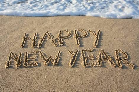 The words happy new year created in sand using a finger.