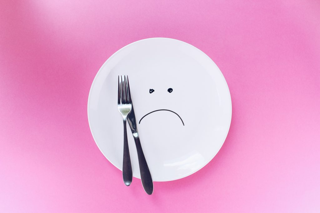 An empty dinner plate with a frown on a pink background.