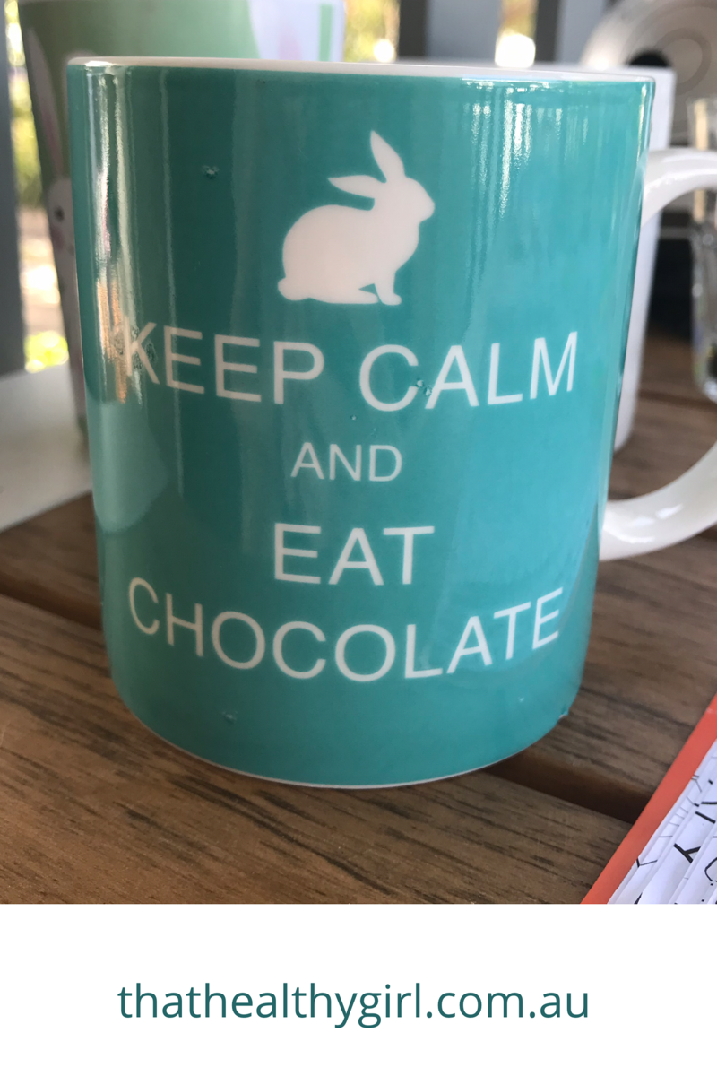 A turquoise coffee cup with the words keep calm and eat chocolate in white font