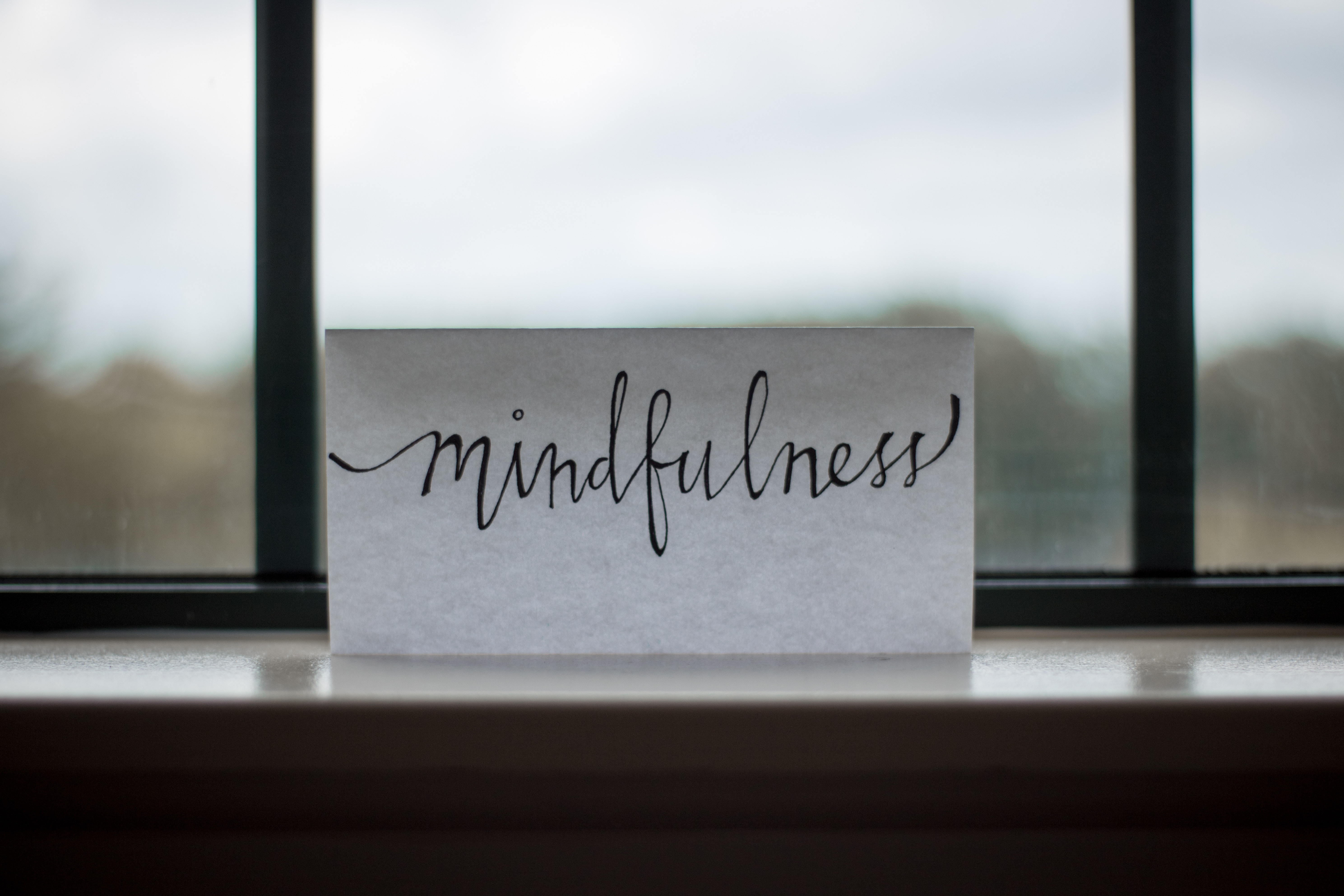 Notecard with the word mindfullness, resting on a window sill.