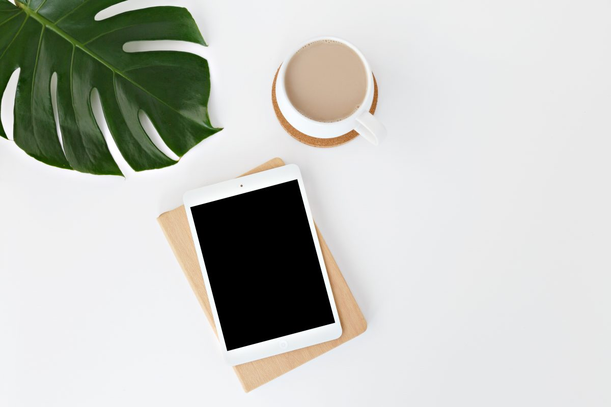 Brisbane Dietitian locations, an ipad, cup of tea and green frond in a vase on a table