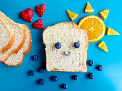 A slice of white bread on a blue background, decorated with fruit to make a smiling face